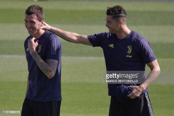 Juventus' Portuguese forward Cristiano Ronaldo jokes with Juventus' Croatian forward Mario Mandzukic during a training session on April 15 2019 at...