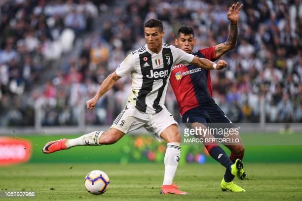Juventus' Portuguese forward Cristiano Ronaldo kicks the ball under pressure from Genoa's Argentine defender Cristian Romero during the Italian Serie...