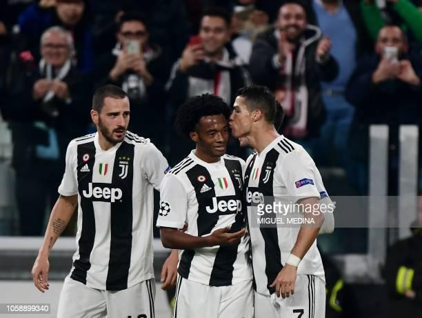Juventus' Portuguese forward Cristiano Ronaldo kisses Juventus' Colombian midfielder Juan Cuadrado as Juventus' Italian defender Leonardo Bonucci...