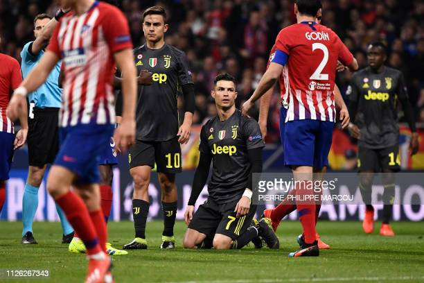 Juventus' Portuguese forward Cristiano Ronaldo kneels on the field during the UEFA Champions League round of 16 first leg football match between Club...