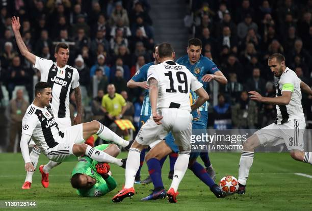 Juventus' Portuguese forward Cristiano Ronaldo l collides with Atletico Madrid's Slovenian goalkeeper Jan Oblak during the UEFA Champions League...