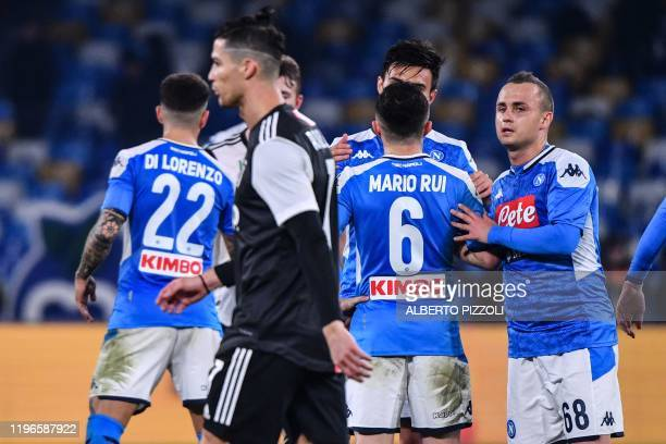 Juventus' Portuguese forward Cristiano Ronaldo leaves the pitch as Napoli's Slovakian midfielder Stanislav Lobotka celebrates with teammates at the...