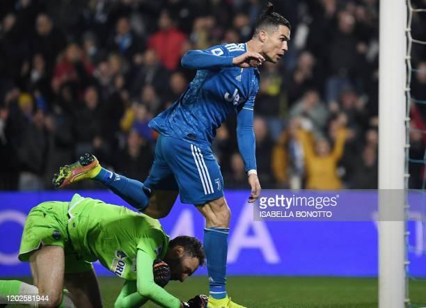 Juventus' Portuguese forward Cristiano Ronaldo opens the scoring past Spal's Albanian goalkeeper Etrit Berisha during the Italian Serie A football...