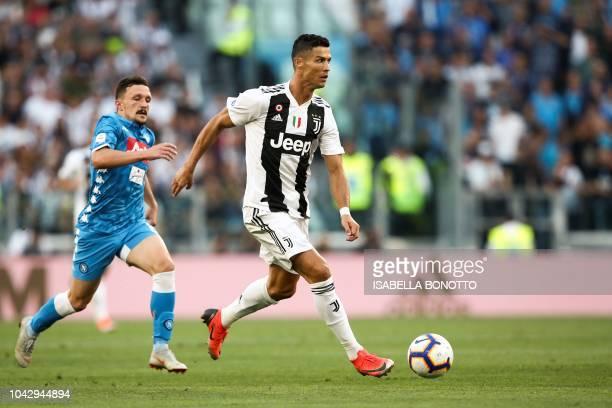 Juventus' Portuguese forward Cristiano Ronaldo outruns Napoli's Portuguese defender Mario Rui during the Italian Serie A football match Juventus vs...