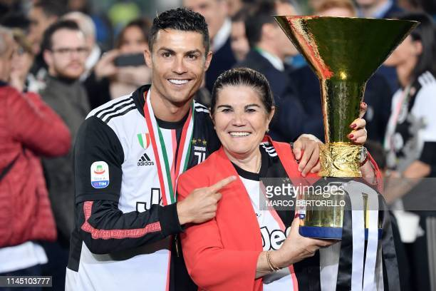 Juventus' Portuguese forward Cristiano Ronaldo poses with his mother holding the Italian Champion's trophy at the end of the Italian Serie A football...