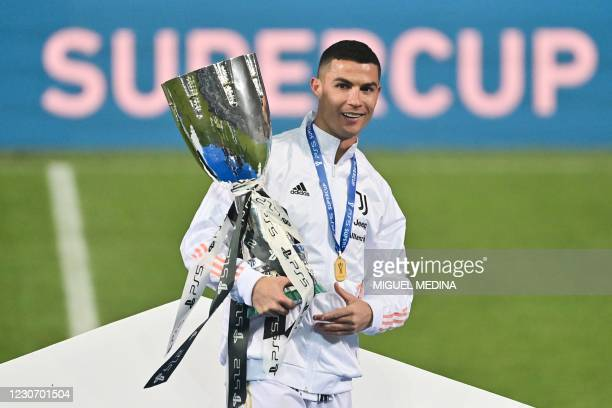 Juventus' Portuguese forward Cristiano Ronaldo poses with the winners' trophy after the Italian Super Cup football match between Juventus and Napoli...