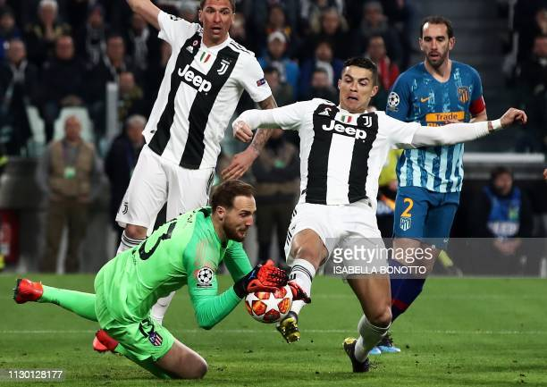 Juventus' Portuguese forward Cristiano Ronaldo reaches out to the ball grabed by Atletico Madrid's Slovenian goalkeeper Jan Oblak during the UEFA...