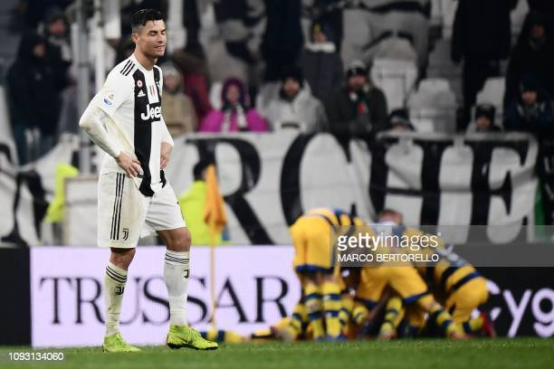 Juventus' Portuguese forward Cristiano Ronaldo reacts after Parma scored a last second equalizer and its players celebrate during the Italian Serie A...