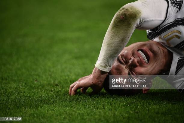 Juventus' Portuguese forward Cristiano Ronaldo reacts in pain after falling during the UEFA Champions League round of 16 second leg football match...