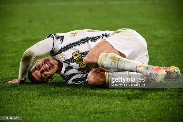 Juventus' Portuguese forward Cristiano Ronaldo reacts in pain after being tackled during the UEFA Champions League round of 16 second leg football...