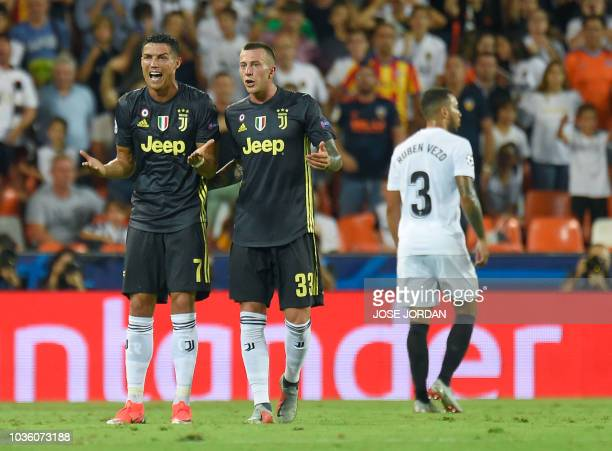 TOPSHOT Juventus' Portuguese forward Cristiano Ronaldo reacts next to Juventus' Italian midfielder Federico Bernardeschi after receiving a red card...