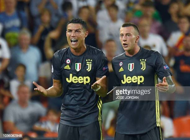 Juventus' Portuguese forward Cristiano Ronaldo reacts next to Juventus' Italian midfielder Federico Bernardeschi after receiving a red card during...