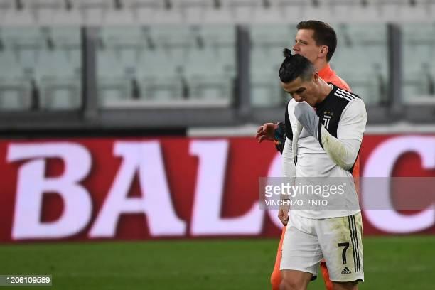 Juventus' Portuguese forward Cristiano Ronaldo reacts past Juventus' Polish goalkeeper Wojciech Szczesny as they celebrate their victory over Inter...