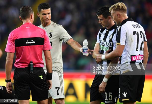 Juventus' Portuguese forward Cristiano Ronaldo shares a bottle of water with Udinese's Serbian midfielder Petar Micin and Czech midfielder Antonin...