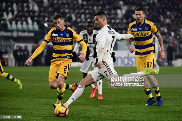 Juventus' Portuguese forward Cristiano Ronaldo shoots on goal despite Parma's Italian defender Simone Iacoponi during the Italian Serie A football...