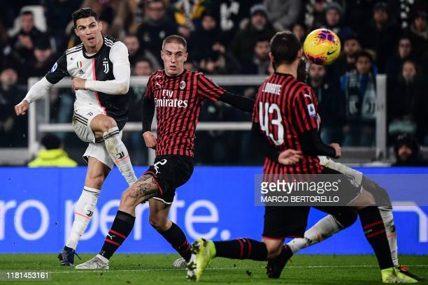 Juventus' Portuguese forward Cristiano Ronaldo shoots on goal despite AC Milan's Italian defender Andrea Conti during the Italian Serie A football...
