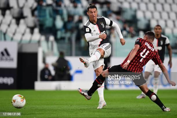 Juventus' Portuguese forward Cristiano Ronaldo shoots on goal despite AC Milan's Algerian defender Ismael Bennacer during the Italian Cup semifinal...