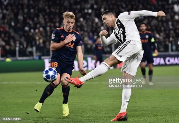 Juventus' Portuguese forward Cristiano Ronaldo shoots on goal past Valencia's Danish midfielder Daniel Wass during the UEFA Champions League group H...
