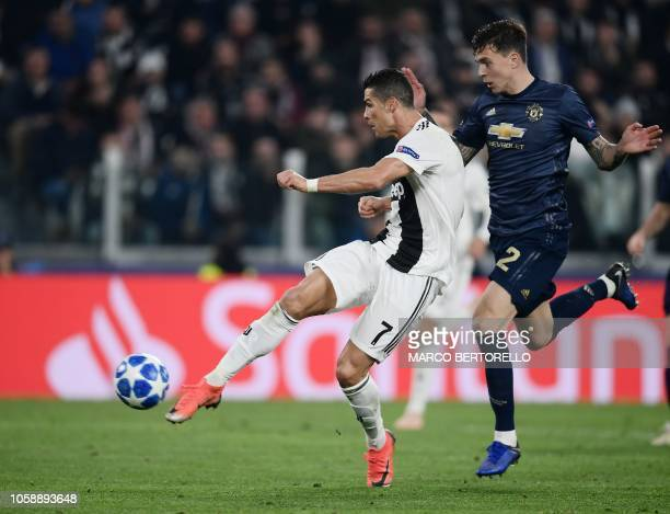 Juventus' Portuguese forward Cristiano Ronaldo shoots to open the scoring despite Manchester United's Swedish defender Victor Lindelof during the...