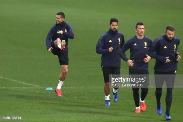 Juventus' Portuguese forward Cristiano Ronaldo stretches as Juventus' Italian defender Andrea Barzagli Juventus' Croatian forward Mario Mandzukic and...