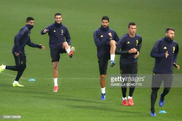 Juventus' Portuguese forward Cristiano Ronaldo stretches as Juventus' Italian defender Andrea Barzagli Juventus' Croatian forward Mario Mandzukic...