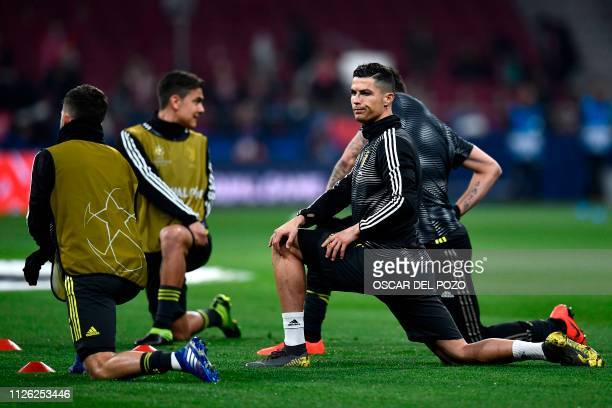Juventus' Portuguese forward Cristiano Ronaldo stretches with teammates as they warm up before the UEFA Champions League round of 16 first leg...