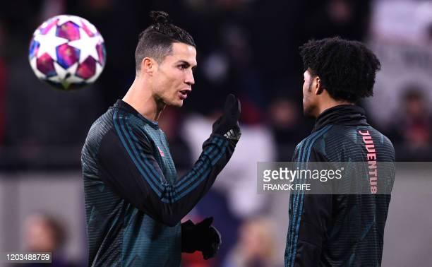 Juventus' Portuguese forward Cristiano Ronaldo talks with Juventus' Colombian midfielder Juan Cuadrado during the warm up prior the UEFA Champions...