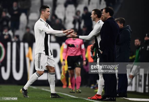 Juventus' Portuguese forward Cristiano Ronaldo taps hands as he is replaced by Juventus' Italian forward Federico Bernardeschi as Juventus' Italian...