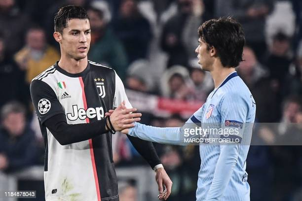 Juventus' Portuguese forward Cristiano Ronaldo taps hands with Atletico Madrid's Portuguese forward Joao Felix at the end of the UEFA Champions...