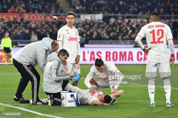 Juventus' Portuguese forward Cristiano Ronaldo tends to Juventus' Turkish defender Merih Demiral after he was injured during the Italian Serie A...