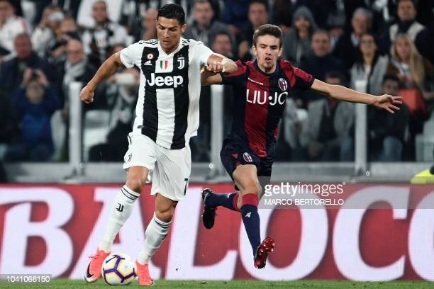 Juventus' Portuguese forward Cristiano Ronaldo vies for the ball with Bologna's Hungarian midfielder Adam Nagy during the Italian Serie A football...