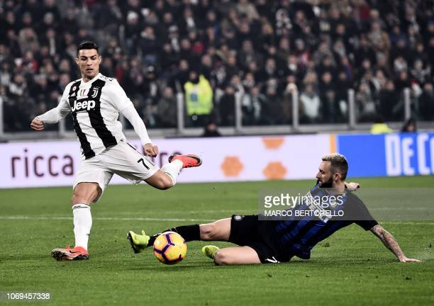 Juventus' Portuguese forward Cristiano Ronaldo vies for the ball with Inter Milan's Croatian midfielder Marcelo Brozovic during the Serie A football...