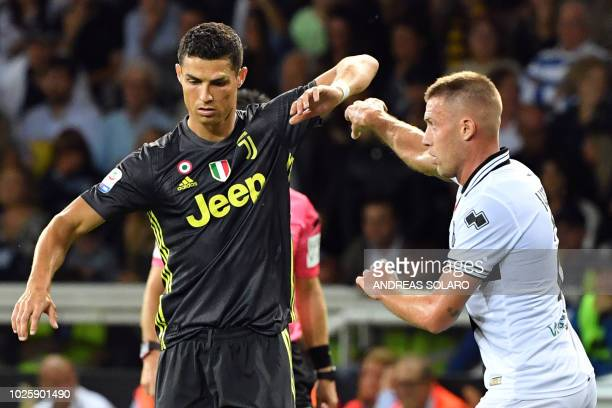 Juventus' Portuguese forward Cristiano Ronaldo vies with Parma's Italian defender Simone Iacoponi during the Italian Serie A football match Parma vs...