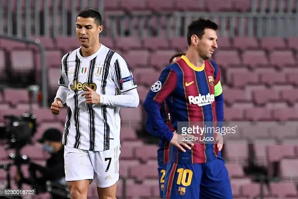 Juventus' Portuguese forward Cristiano Ronaldo walks past Barcelona's Argentinian forward Lionel Messi during the UEFA Champions League group G...