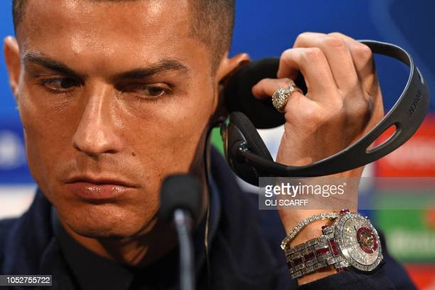 Juventus' Portuguese striker Cristiano Ronaldo listens to his headphones during a press conference at Old Trafford in Manchester, north west England...
