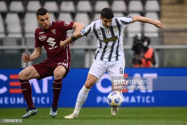 Juventus' Spanish forward Alvaro Morata outflanks Torino's Italian defender Alessandro Buongiorno during the Italian Serie A football match Torino vs...