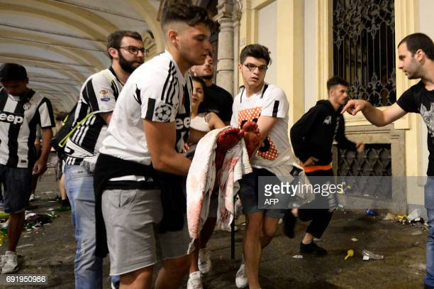 Juventus' supporters carry an injured woman in Piazza San Carlo after a panic movement in the fanzone where thousands of Juventus fans were watching...