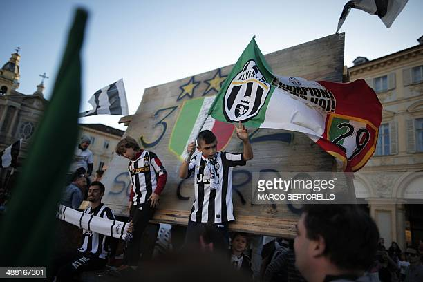 Juventus supporters celebrate after their football club won the Italian Scudetto in Piazza San Carlo in Turin on May 4, 2014. Juventus won their...