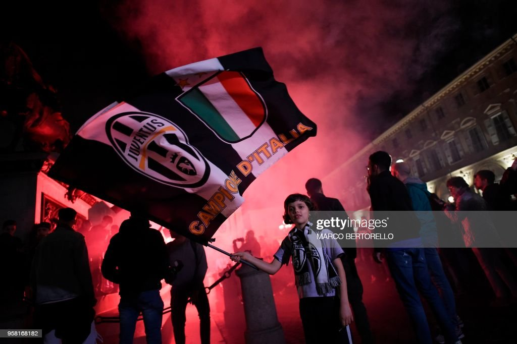 TOPSHOT - Juventus' supporters celebrate in central Turin after their team won a seventh straight Serie A title 'scudetto' after a goalless draw against ten-man Roma at the Stadio Olimpico, on May 13, 2018. - The Turin giants become the first team to complete the league and Cup double for four consecutive seasons. It is the 34th Scudetto in Juventus's history.