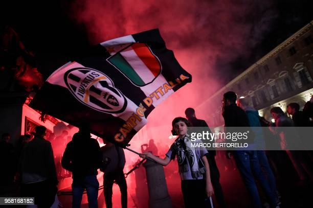 TOPSHOT Juventus' supporters celebrate in central Turin after their team won a seventh straight Serie A title scudetto after a goalless draw against...