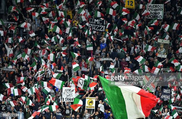 Juventus supporters cheer and wave flags during the Italian Serie A football match Juventus vs Fiorentina on September 20 2017 at the Allianz Stadium...
