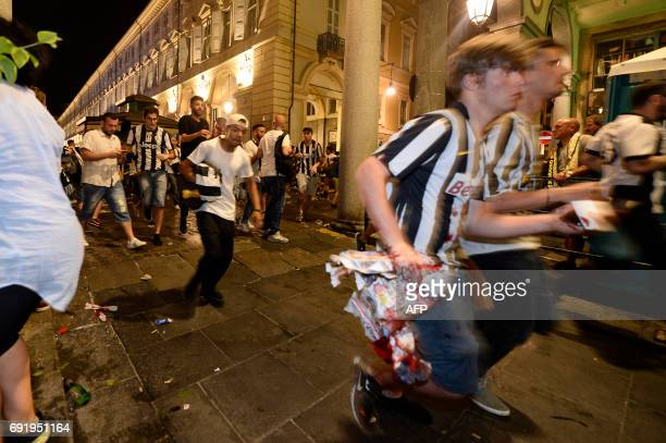 Juventus supporters evacuate Piazza San Carlo after a panic movement in the fanzone where thousands of Juventus fans were watching the UEFA Champions...