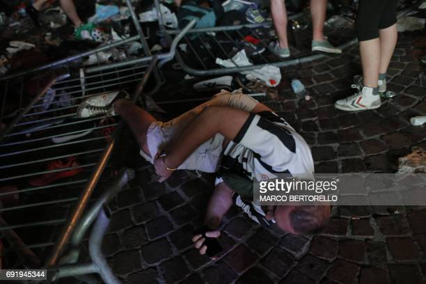 Juventus' supporters falls as he tries to escape the Piazza San Carlo during a panic movement in the fanzone where thousands of Juventus fans were...