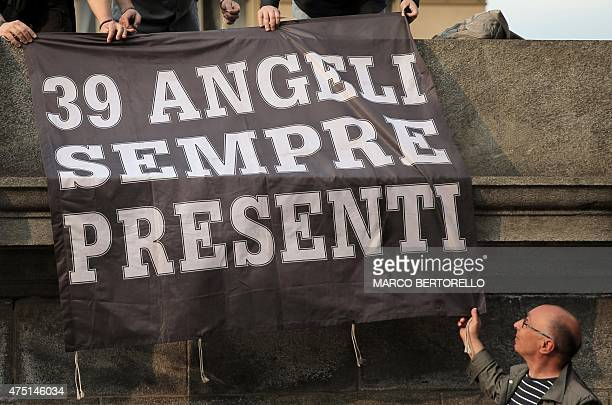 """Juventus supporters hold a banner reading """"39 angels forever"""" outside the Gran Madre di Dio church in Turin on May 29 during a mass to mark the 30th..."""