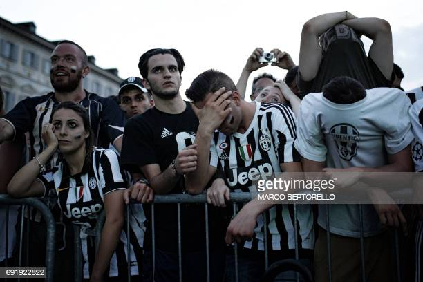 Juventus' supporters react after as they follow the UEFA Champions League Final football match between Juventus and Real Madrid on a giant screen on...
