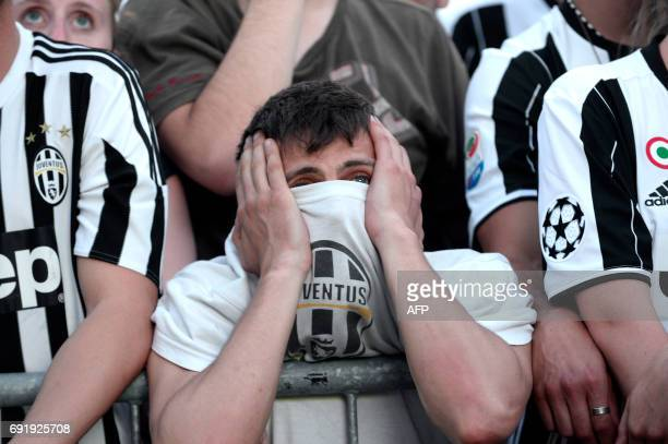 Juventus' supporters react as they follow the UEFA Champions League Final football match between Juventus and Real Madrid on a giant screen on June 3...