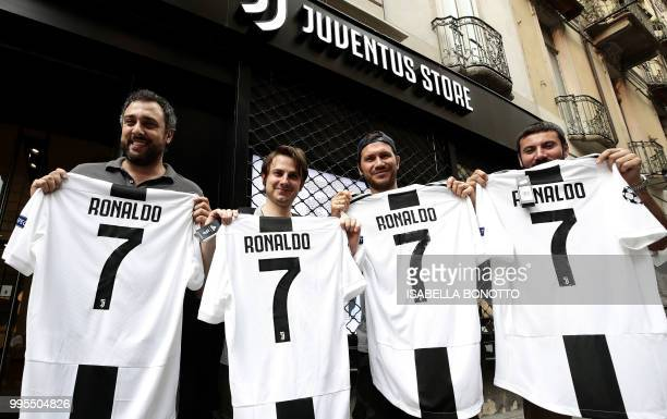 TOPSHOT Juventus' supporters show their Cristiano Ronaldo's Juventus official Jerseys in front of the Juventus store on July 10 2018 in Turin after...