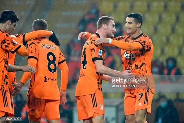 Juventus' Swedish forward Dejan Kulusevski celebrates with Juventus' Portuguese forward Cristiano Ronaldo after opening the scoring during the...