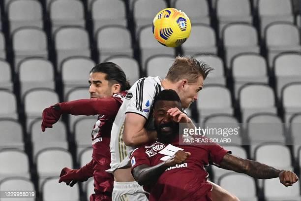 Juventus' Swedish forward Dejan Kulusevski fights for the ball with Torino's Swiss defender Ricardo Rodriguez and Torino's Cameroon defender Nicolas...