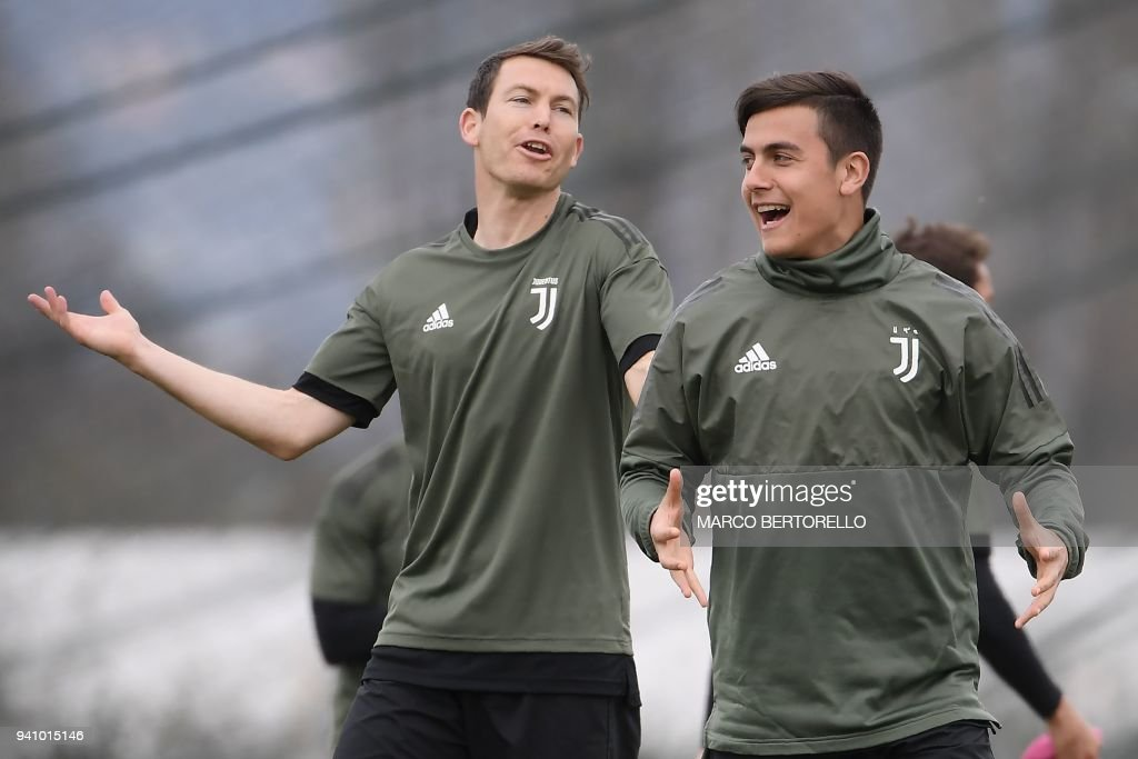 Juventus' Swiss defender Stephan Lichtsteiner (L) and Juventus' Argentinian forward Paulo Dybala attend a training session on the eve of the UEFA Champions League football match Juventus vs Real Madrid on April 2, 2018 at the Juventus training center in Vinovo. /